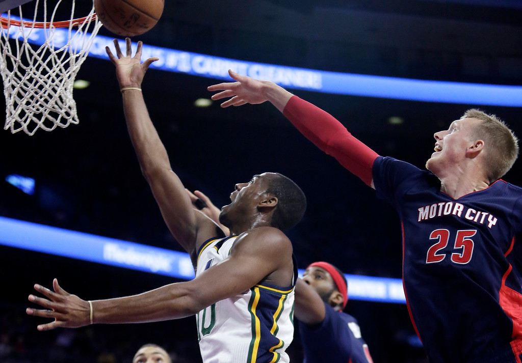 . Utah Jazz\'s Alec Burks goes to the basket past Detroit Pistons\' Kyle Singler (25) during the first half of an NBA basketball game Sunday, Nov. 9, 2014, in Auburn Hills, Mich.  (AP Photo/Duane Burleson)