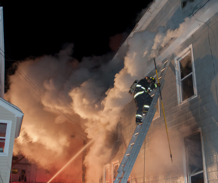 A Gardner FF climbs a ground ladder to vent 2nd floor windows at 403 Chestnut St during a 4th Alm.