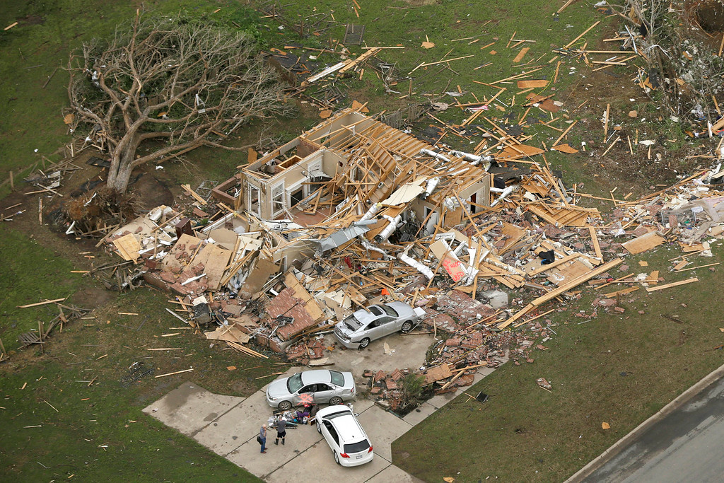 . Two men stand in front of a destroyed house in Mayflower, Ark., Monday, April 28, 2014, after a tornado struck the town late Sunday. (AP Photo/Danny Johnston)
