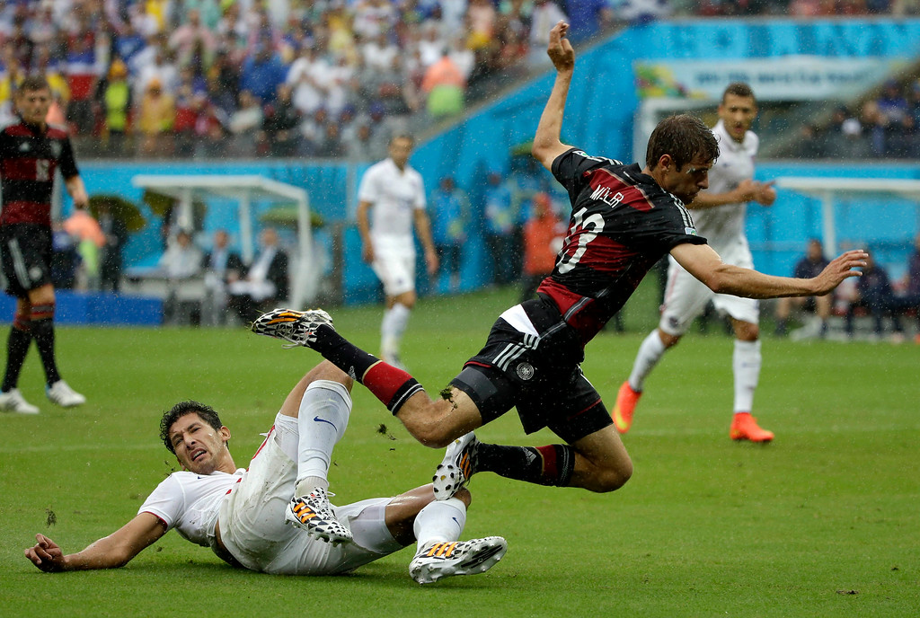 . Germany\'s Thomas Mueller is tripped by United States\' Omar Gonzalez during the group G World Cup soccer match between the USA and Germany at the Arena Pernambuco in Recife, Brazil, Thursday, June 26, 2014. (AP Photo/Ricardo Mazalan)