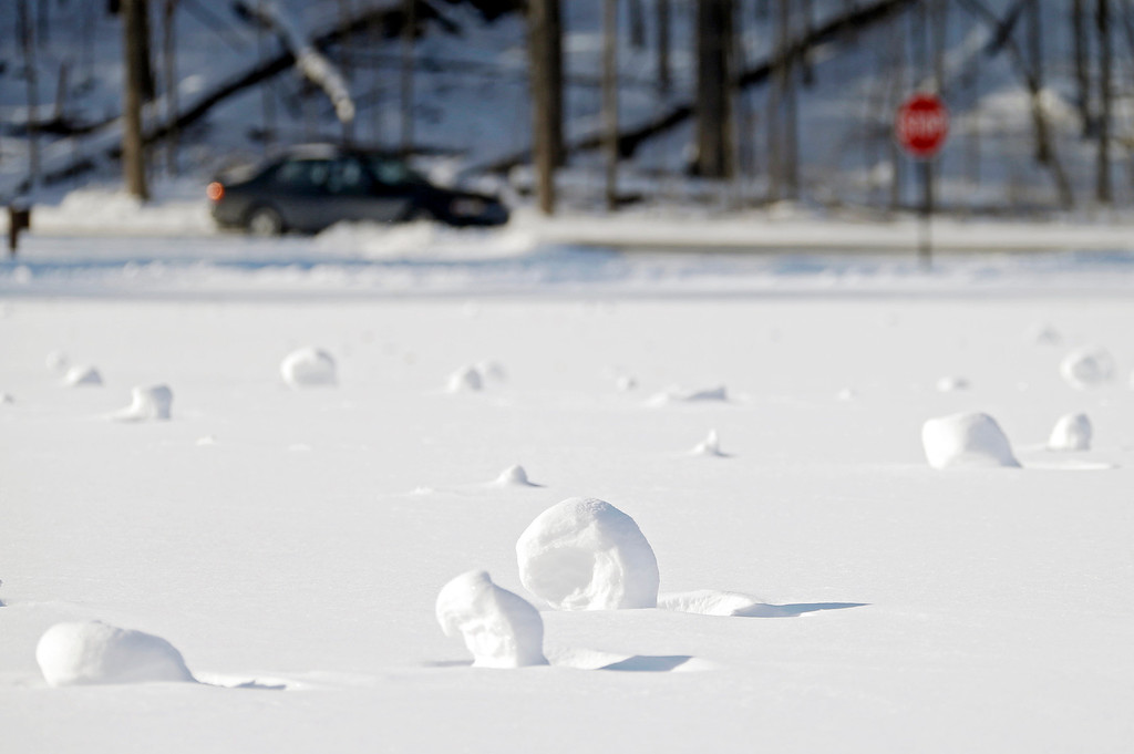 . Snow rollers dot a field at the Cleveland Metroparks Mastic picnic area Tuesday, Jan. 28, 2014, in Fairview Park, Ohio. The snowballs are formed when high winds roll accumulated snow across open areas. The National Weather Service has placed most of Ohio under a wind chill warning until Wednesday. (AP Photo/Mark Duncan)
