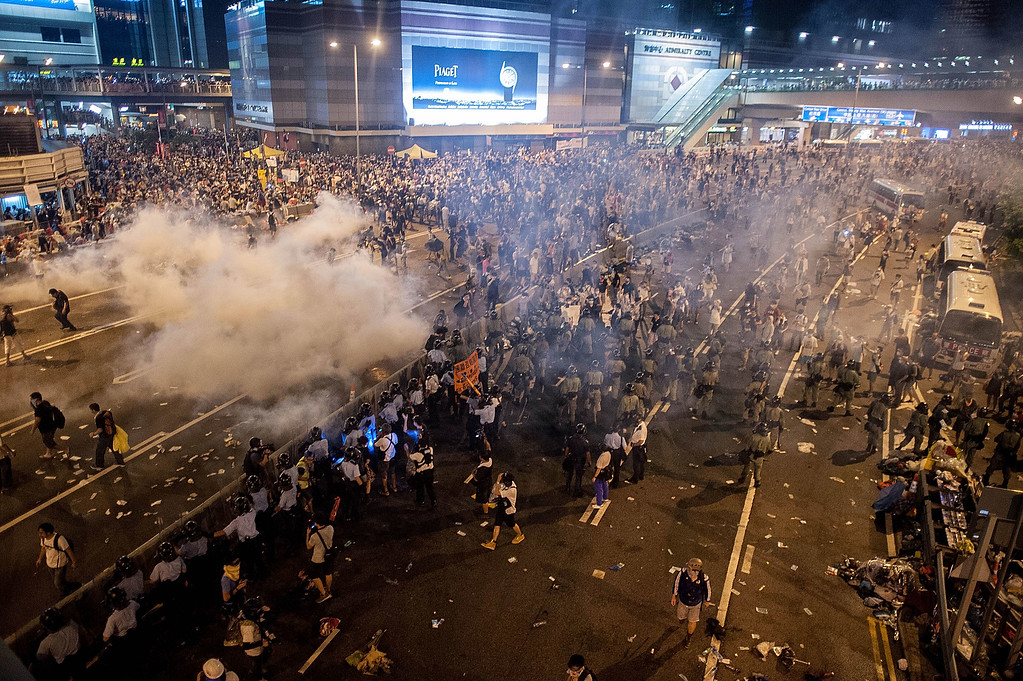 . Demonstrators disperse as tear gas is fired by police during a protest on September 28, 2014 in Hong Kong. Thousands of people kicked off Occupy Central by taking over Connaught Road, one of the major highway in Hong Kong, in protest against Beijing\'s conservative framework for political reform.  (Photo by Anthony Kwan/Getty Images)