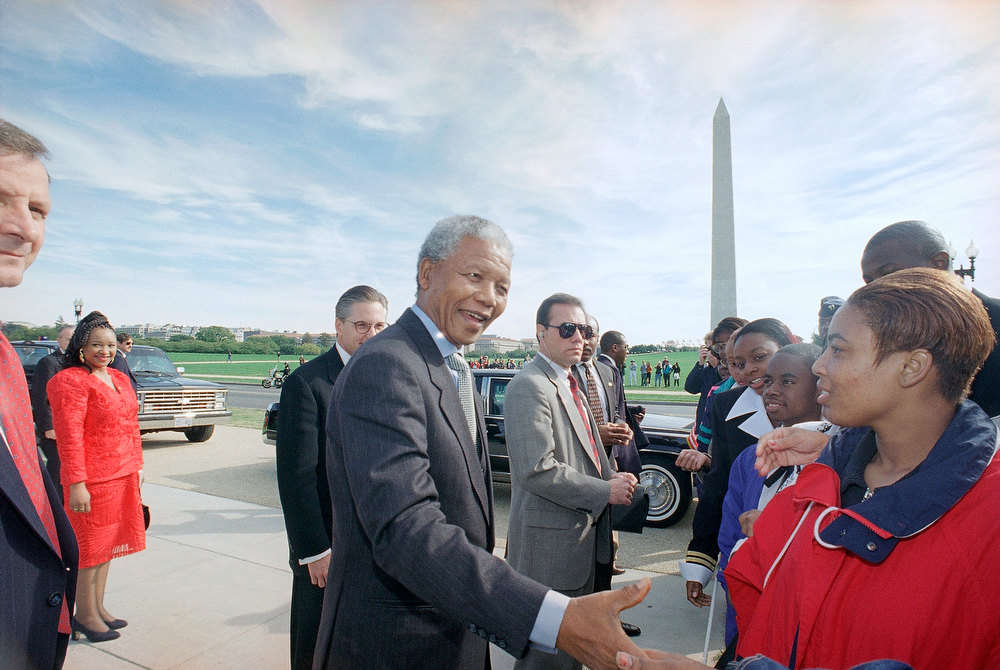 . With the Washington Monument in the background, South African President Nelson Mandela is greeted upon his arrival in Washington by students from Washington\'s Anacostia High School on Tuesday, Oct. 4, 1994.    Afterward President Mandela went to the White House for a meeting with President Bill Clinton. (AP Photo/Charles Tasnadi)