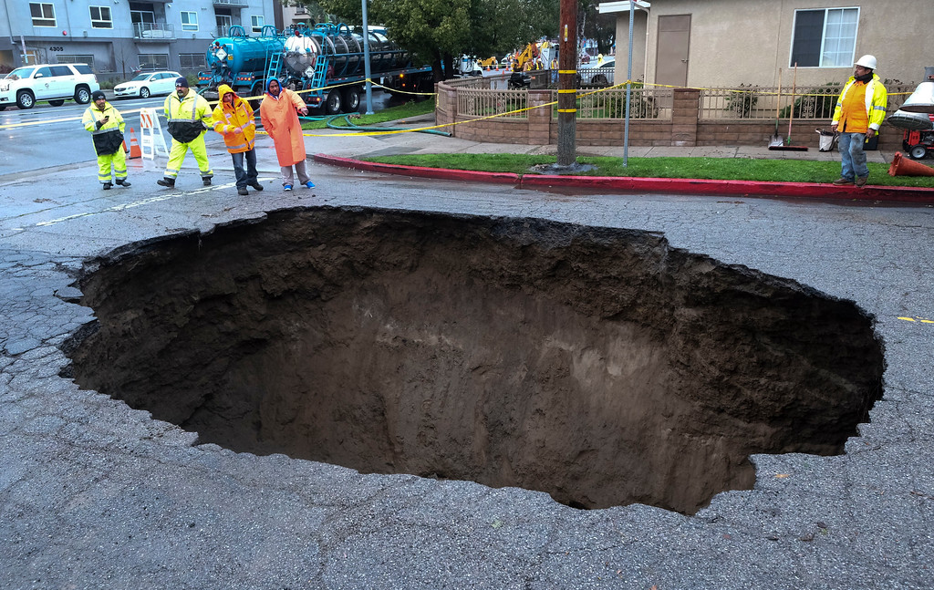 . Inspectors examine a sinkhole Saturday, Feb. 18, 2017, in Studio City, north of Los Angeles. Two vehicles fell into the 20-foot sinkhole on Friday night and firefighters had to rescue one woman who escaped her car but was found standing on her overturned vehicle.  (AP Photo/Ringo H.W. Chiu)