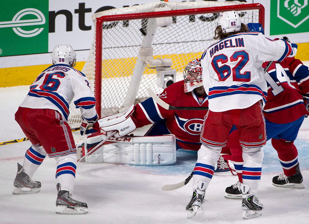 . Montreal Canadiens goalie Carey Price, center, looks over his shoulder as the puck enters the net on a shot by New York Rangers\' Martin St. Louis, left, as Rangers\' Carl Hagelin looks on during the first period in Game 1 of the Eastern Conference finals in the NHL hockey Stanley Cup playoffs in Montreal on Saturday, May 17, 2014. (AP Photo/The Canadian Press, Adrian Wyld)