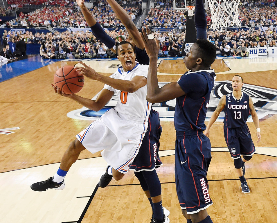 . Florida guard Kasey Hill is defended by Connecticut center Amida Brimah during the second half of the NCAA Final Four tournament college basketball semifinal game Saturday, April 5, 2014, in Arlington, Texas. (AP Photo/Chris Steppig, pool)