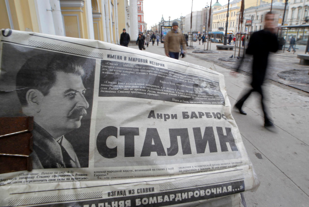 . People pass by a kiosk, with a photograph of the late Soviet leader Josef Stalin on the front page of a newspaper seen in the foreground, on the day of the 60th anniversary of Stalin\'s death in St. Petersburg on March 5, 2013.  REUTERS/Alexander Demianchuk