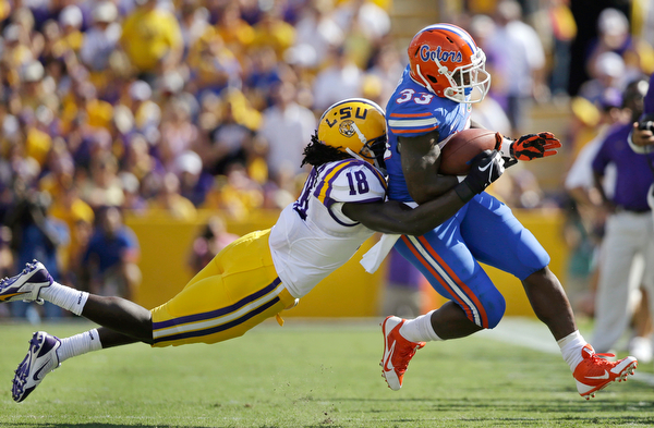. Florida running back Mack Brown (33) is tackled by LSU linebacker Lamin Barrow (18) in the first half of an NCAA college football game in Baton Rouge, La., Saturday, Oct. 12, 2013. (AP Photo/Gerald Herbert)