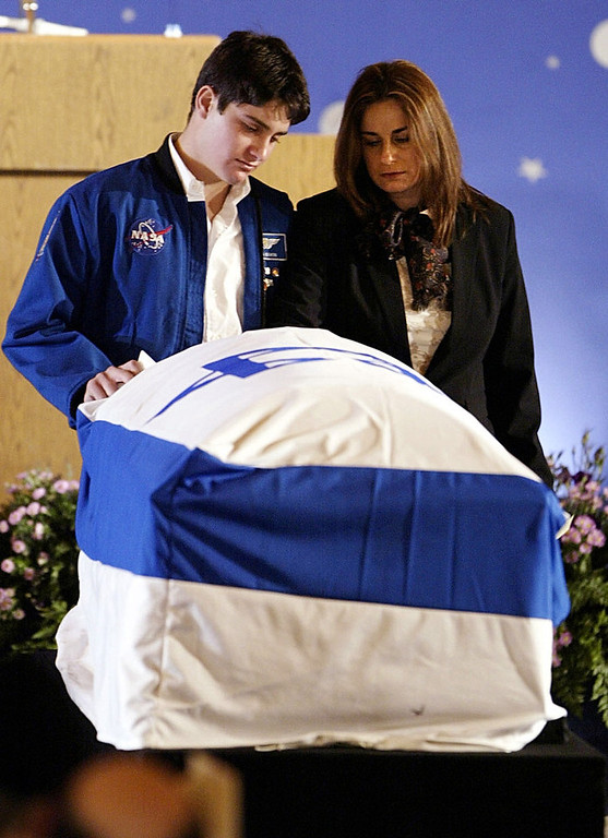 . Rona Ramon, right, and Assaf Ramon, left, widow and eldest son of Israel\'s first astronaut Ilan Ramon pay their respects beside his coffin during a memorial service at Ben Gurion International Airport outside Tel Aviv Feb. 10, 2003.  Ramon, a 48-year-old air force colonel, died with six other astronauts aboard NASA\'s Columbia space shuttle, which splintered in a bright ball of flame as it came down through the Earth\'s atmosphere on Feb. 1, 2003.  Assaf wears his fathers NASA flight jacket. (AP Photo/ Paul Hanna, Pool)