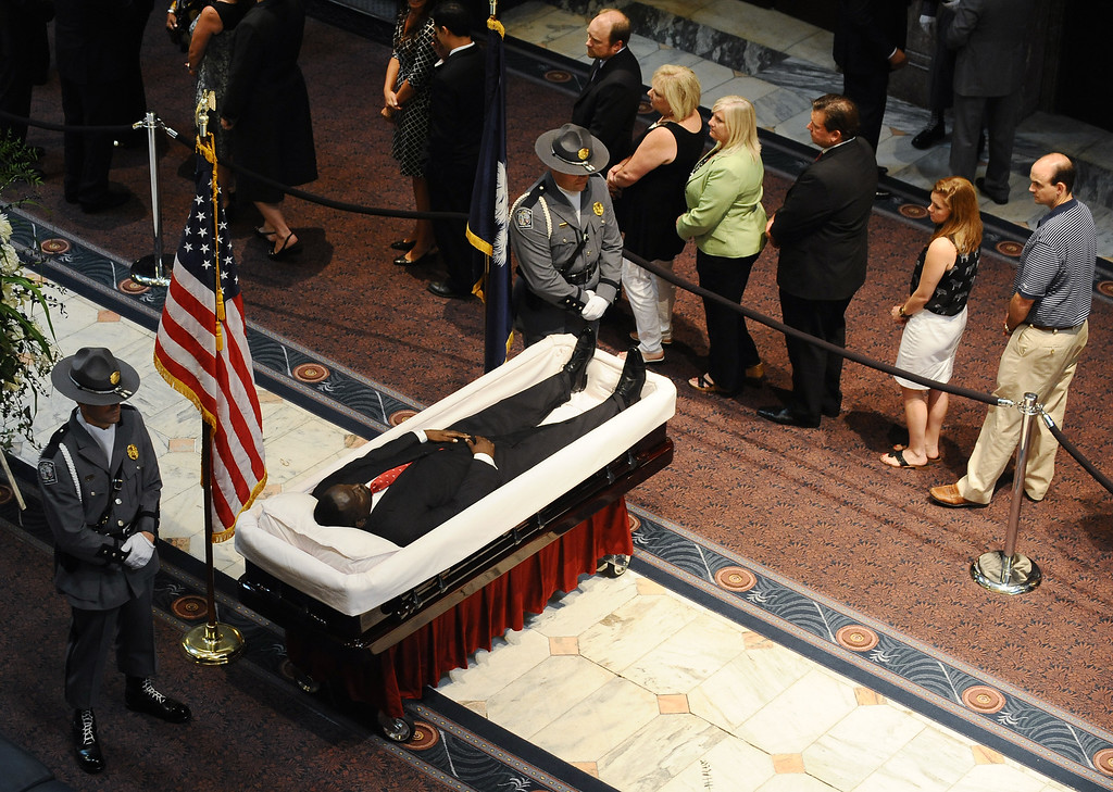. South Carolina Highway Patrol honor guards stand over Sen. Clementa Pinckney\'s body as members of the public file past in the Statehouse, Wednesday, June 24, 2015, in Columbia, S.C.  President Barack Obama is scheduled to deliver the eulogy at Pinckney\'s funeral Friday morning at the College of Charleston. (AP Photo/Rainier Ehrhardt)