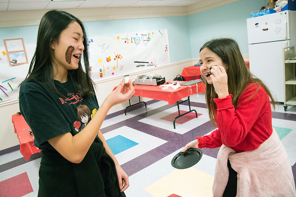 02/14/20 Wesley Bunnell | StaffrrThe Plainville Public Library held candy making during the afternoon in different sessions for K through teenagers. Christine Dai, age 14, and Janessa Freitas, age 15, laugh as they smear chocolate covered marshmallows on their cheeks.