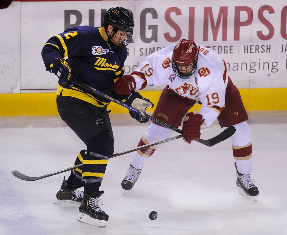 . DENVER, CO. - OCTOBER 12: Merrimack defenseman Craig Wyszomirski (2) fought for the puck with Denver center Daniel Doremus (19) in the first period. The University of Denver hockey team hosted Merrimack at Magness Arena, Saturday night, October 12, 2013. Photo By Karl Gehring/The Denver Post