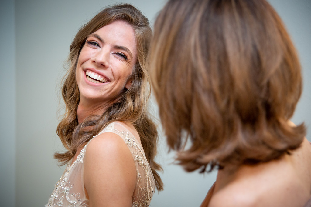 bride wearing an off white lace dress smiling as she gets ready for her wedding