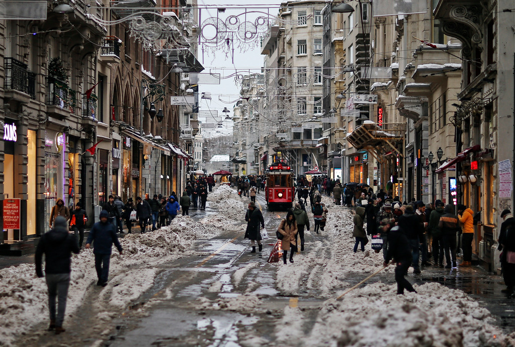 . People walk through the slush in Istiklal Avenue, the city\'s main shopping road, in Istanbul, Tuesday, Jan. 10, 2017. Heavy snow continued to clog roads, shipping traffic in Bosphorus and forced again hundreds of flight cancellations in the Turkish metropolis.(AP Photos/Emrah Gurel)