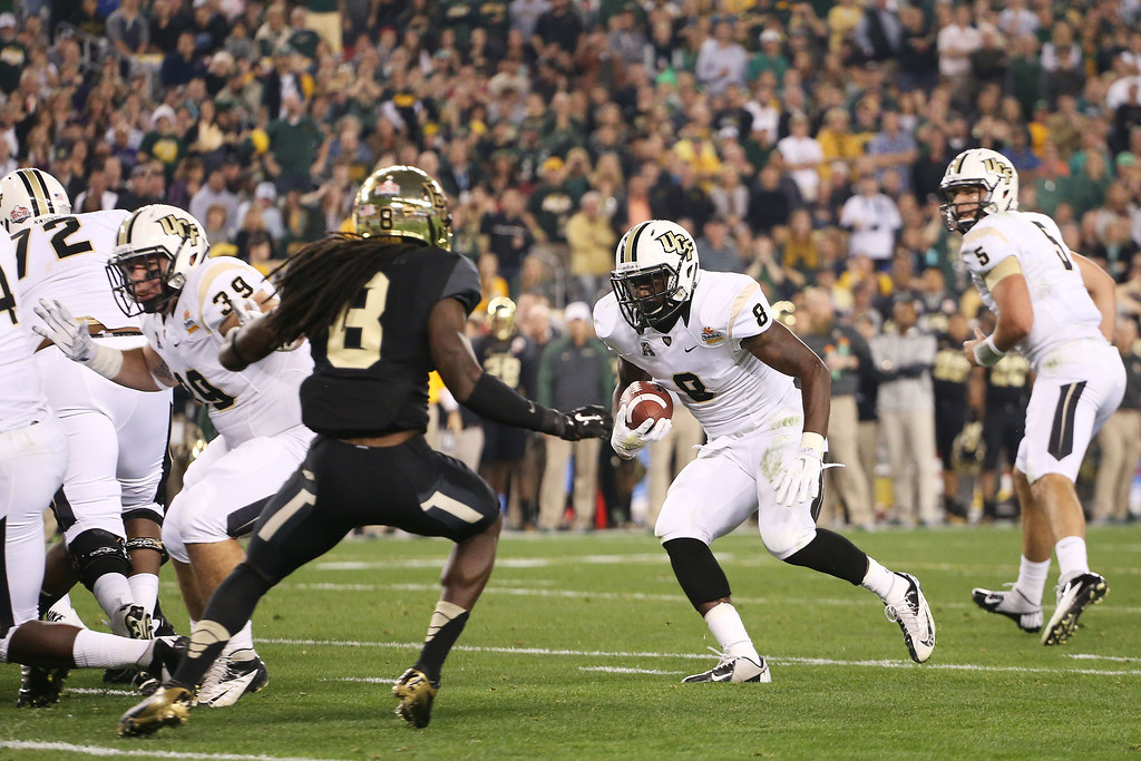 . GLENDALE, AZ - JANUARY 01:  Storm Johnson #8 of the UCF Knights runs the ball against the defense of K.J. Morton #8 of the Baylor Bears in the first quarter during the Tostitos Fiesta Bowl at University of Phoenix Stadium on January 1, 2014 in Glendale, Arizona.  (Photo by Christian Petersen/Getty Images)