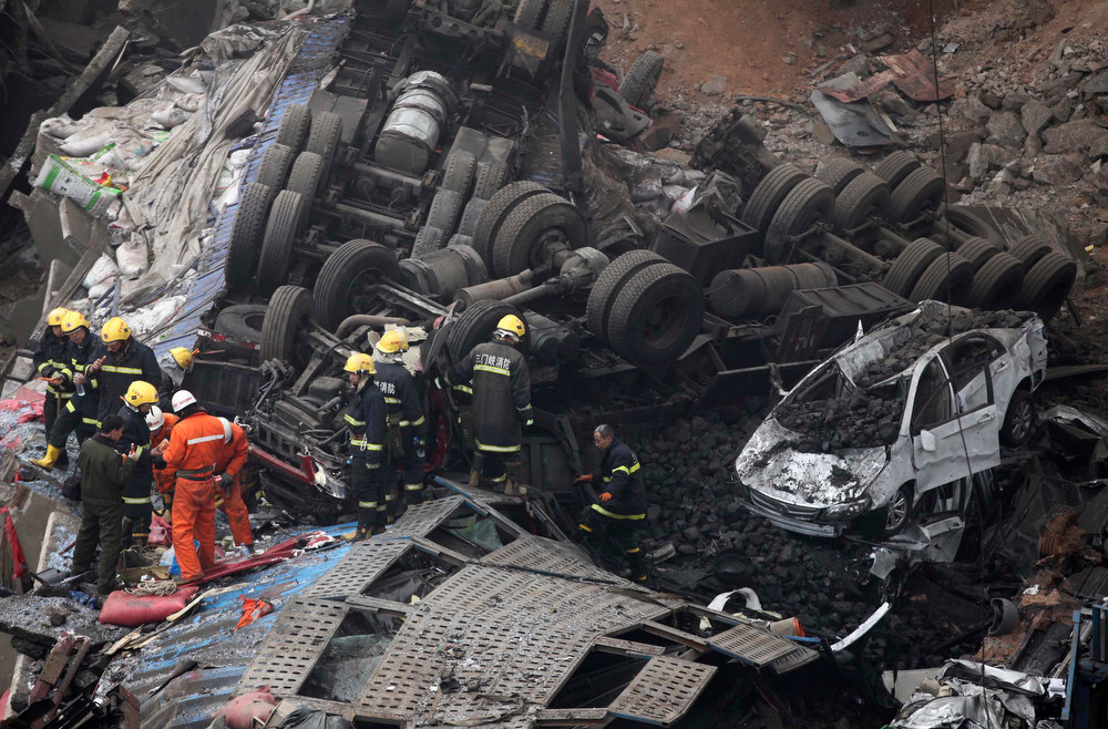 . Rescuers look for survivors near a wreckage of vehicles after a expressway bridge partially collapsed on the Lianhuo highway in Mianchi county, Henan province February 1, 2013. According to Xinhua News Agency, five people have died and eight others were injured after an expressway bridge partially collapsed due to a truck explosion Friday morning in central China\'s Henan Province, local government said. The truck was loaded with fireworks and the explosion caused several vehicles to tumble from the 30-meter-high bridge in Mianchi County, a spokesperson of Sanmenxia told Xinhua on Friday afternoon. REUTERS/Carlf Zhang