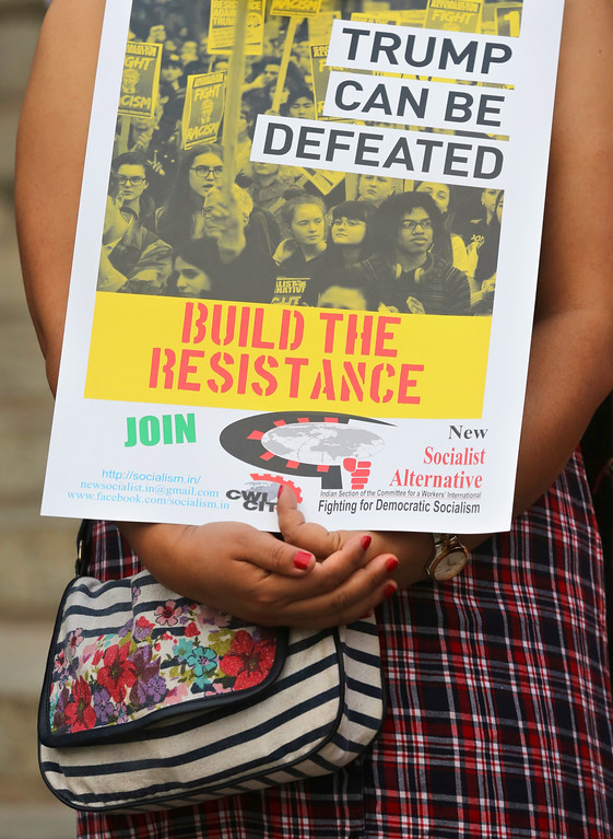. An Indian woman holds a placard as she participates in a protest demonstration against U.S. President Donald Trump in Bangalore, India, Saturday, Jan. 21, 2017. The protest is part of a worldwide day of actions following the inauguration of U.S President Donald Trump. (AP Photo/Aijaz Rahi)