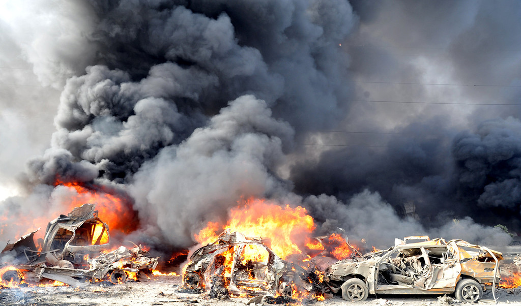 """. A handout picture from the Syrian Arab News Agency (SANA) shows smoke rising from burning cars at the site of twin blasts in Damascus on May 10, 2012. Two powerful blasts in quick succession rocked the Syrian capital at morning rush hour, killing and wounding dozens of people, state television said, blaming the attacks on \""""terrorists.\"""" -/AFP/GettyImages"""