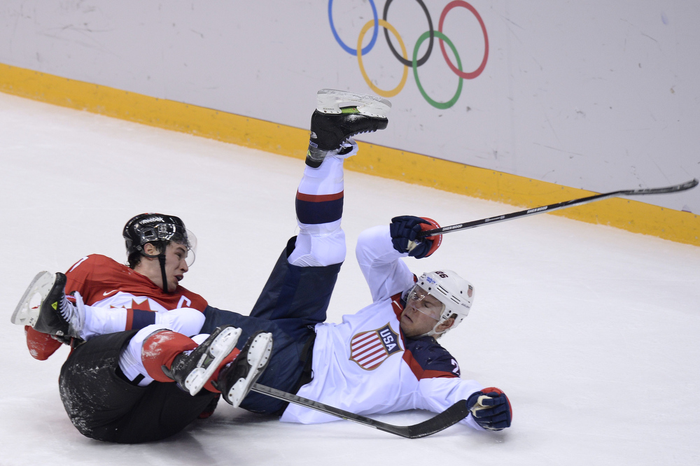 . Canada\'s Sidney Crosby (L) and US Paul Stastny fall on ice during the Men\'s Ice Hockey Semifinals USA vs Canada at the Bolshoy Ice Dome during the Sochi Winter Olympics on February 21, 2014.     ALEXANDER NEMENOV/AFP/Getty Images