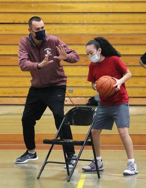 Lowell High girls basketball practice. Head coach Dan Sargent demonstrates a move to sophomore Deborah Garcia. (SUN/Julia Malakie)