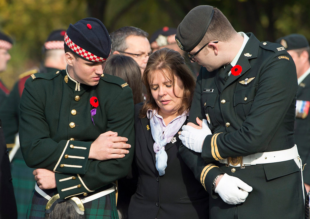 . Kathy Cirillo is comforted by soldiers during the funeral procession for her son Cpl. Nathan Cirillo in Hamilton, Ontario, on Tuesday, Oct. 28, 2014.   (AP Photo/The Canadian Press, Frank Gunn)