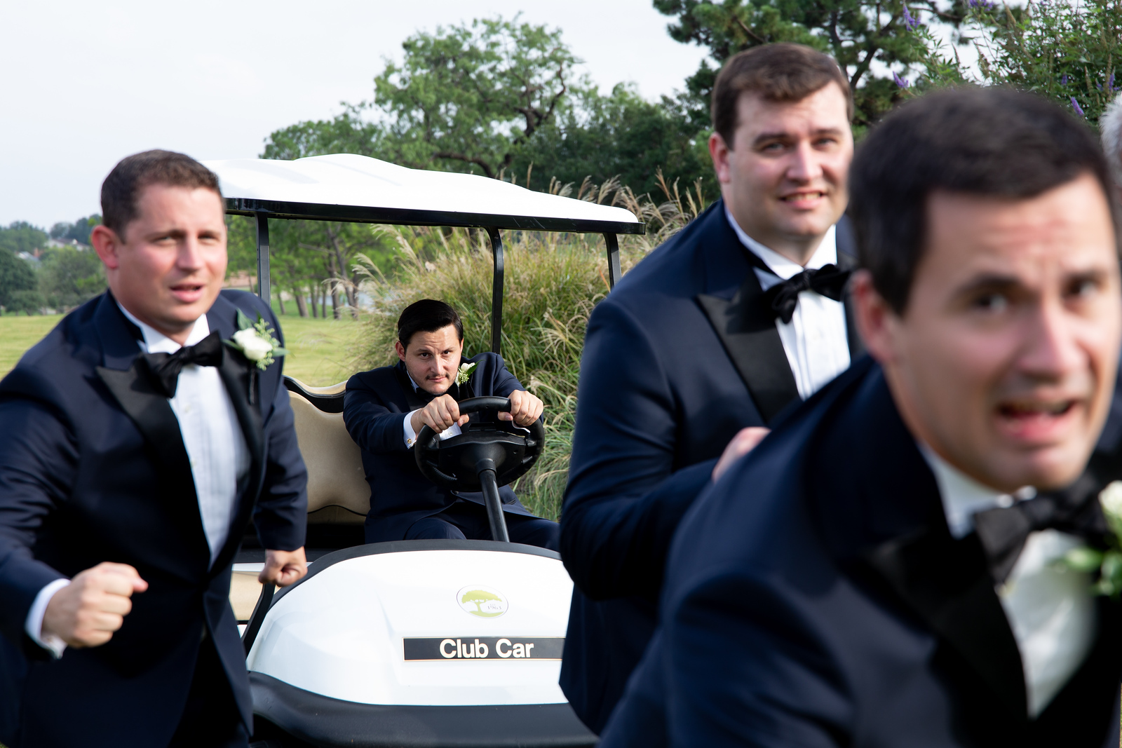 groom jokingly driving a golf cart towards his groomsmen as the run away