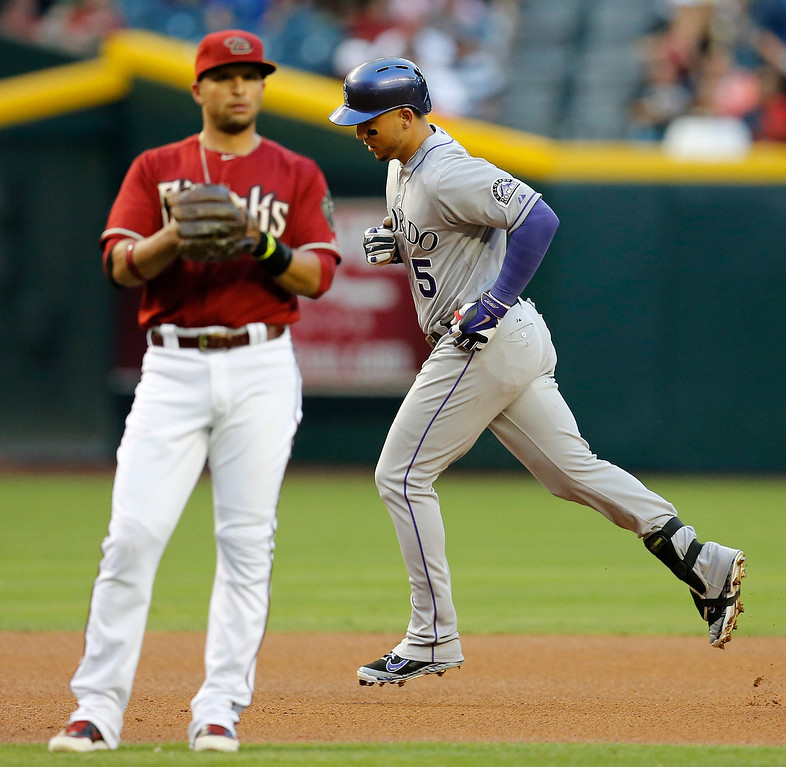 . Colorado Rockies\' Carlos Gonzalez, right, rounds the bases after hitting a two-run home run as Arizona Diamondbacks\' Martin Prado looks away during the first inning of a baseball game on Wednesday, April 30, 2014, in Phoenix. (AP Photo/Matt York)