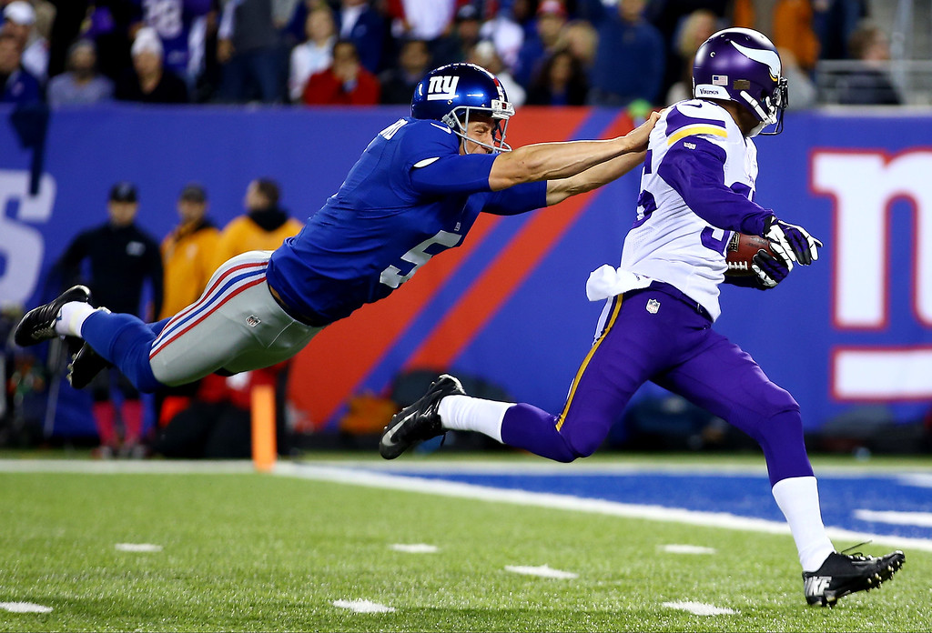. Punter Steve Weatherford #5 of the New York Giants tries to tackle cornerback Marcus Sherels #35 of the Minnesota Vikings as he returns a punt for a touchdown in the first quarter during a game at MetLife Stadium on October 21, 2013 in East Rutherford, New Jersey.  (Photo by Al Bello/Getty Images)
