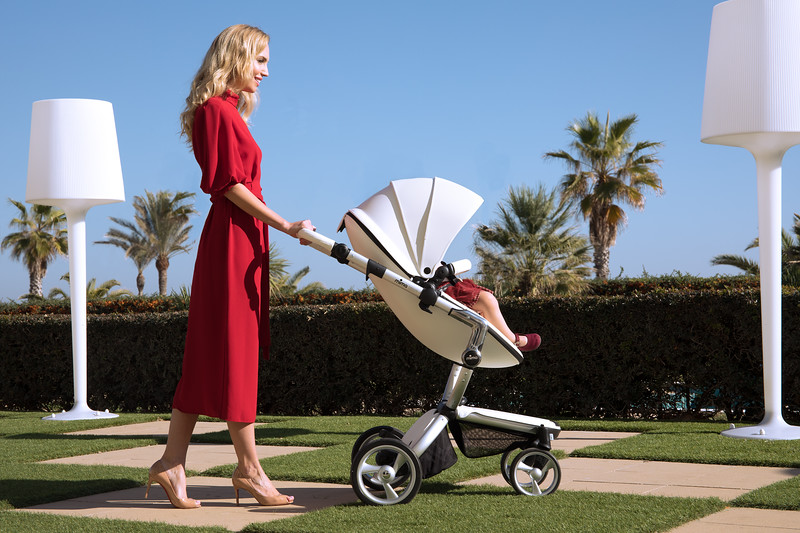 Mima_Xari_Lifestyle_Snow_White_Aluminium_Chassis_Pod_Mum_In_Red_Dress_Walking_On_Checked_Grass_With_Pushchair.jpg