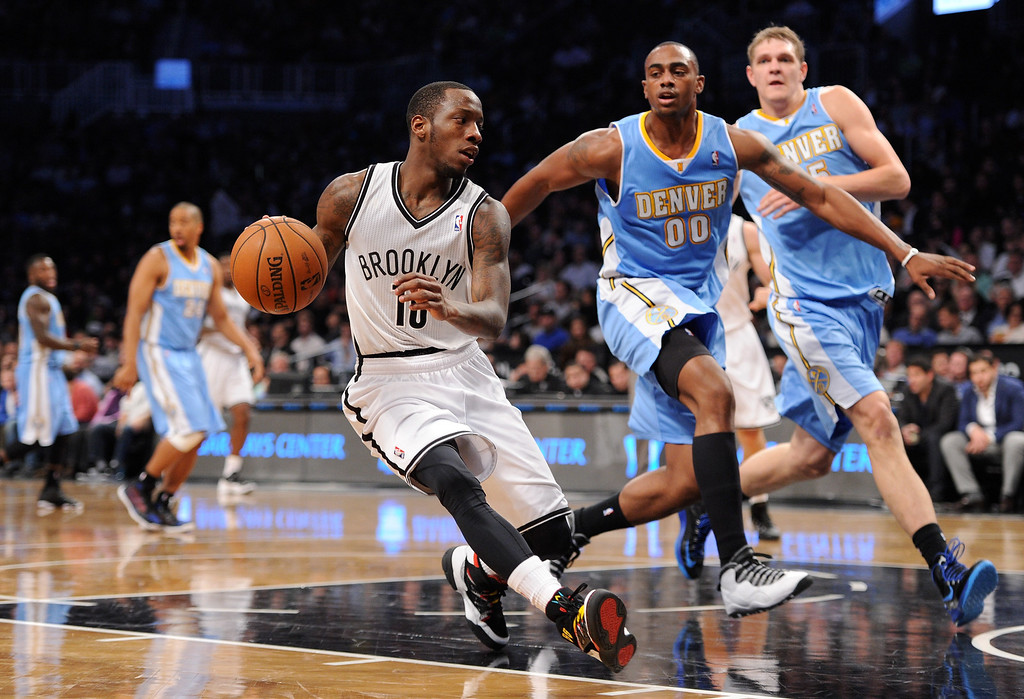 . NEW YORK, NY - DECEMBER 03:  Tyshawn Taylor #10 of the Brooklyn Nets drives against Darrell Arthur #00 of the Denver Nuggets during the second half at Barclays Center on December 3, 2013 in the Brooklyn borough of New York City. The Nuggets defeat the Nets 111-87. (Photo by Maddie Meyer/Getty Images)