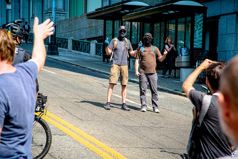 Antifa supporters exchange hand gestures with the opposition as they walk by.