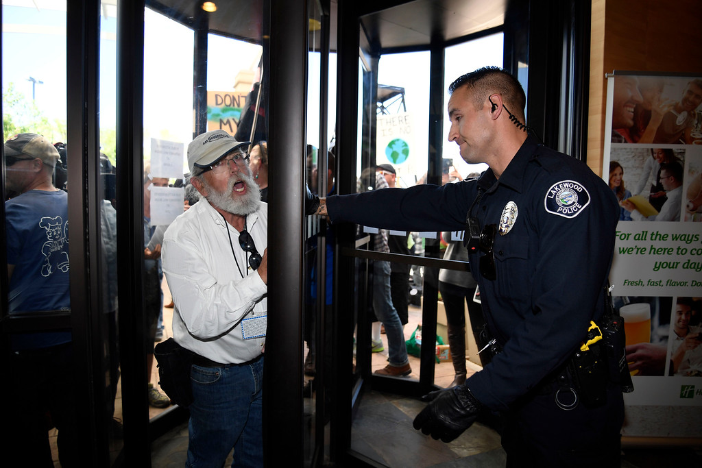 . LAKEWOOD, CO - MAY 12: Lakewood police officer tries to keep a protester out of the hotel as hundreds of Colorado community, climate and fracking activists rush inside the lobby to the Holiday Inn to protest a Bureau of Land Management oil and gas lease auction May 12, 2016 in Lakewood. The group rallied to disrupt the auction which was being held inside the hotel. The groups plan was to demand that public lands be no longer drilled, mined, or fracked. The protest was part of a global week of action focused on citizen action to keep fossil fuels in the ground and promote clean renewable energy, and comes days after the Colorado Supreme Court denied local authority to regulate fracking. (Photo By John Leyba/The Denver Post)