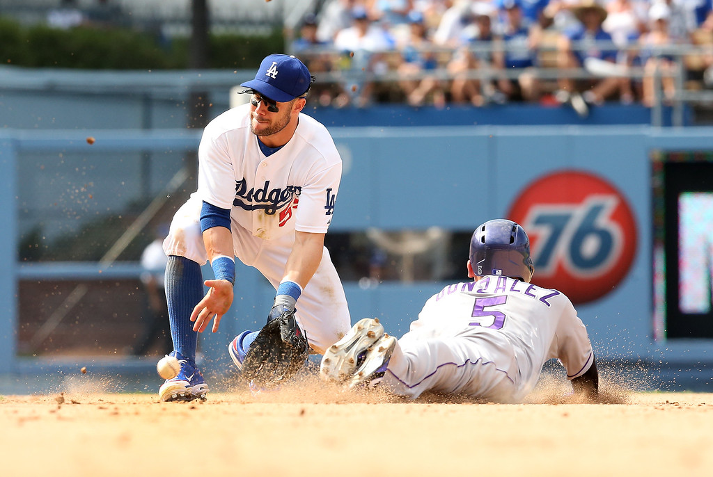 . Carlos Gonzalez #5 of the Colorado Rockies slides into second with a stolen base head of the throw to second baseman Skip Schumaker #55 of the Los Angeles Dodgers in the ninth inning at Dodger Stadium on July 14, 2013 in Los Angeles, California.  The Rockies won 3-1.  (Photo by Stephen Dunn/Getty Images)