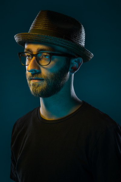 Portrait of a man wearing a weaved fedora and glasses.