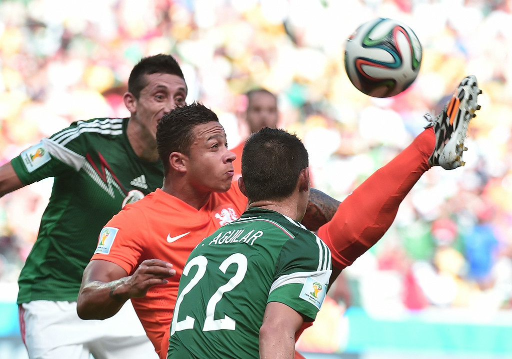 . Netherlands\' forward Memphis Depay (C) vies for the ball with Mexico\'s defender Paul Aguilar (R) during a Round of 16 football match between Netherlands and Mexico at Castelao Stadium in Fortaleza during the 2014 FIFA World Cup on June 29, 2014. AFP PHOTO / DAMIEN MEYER