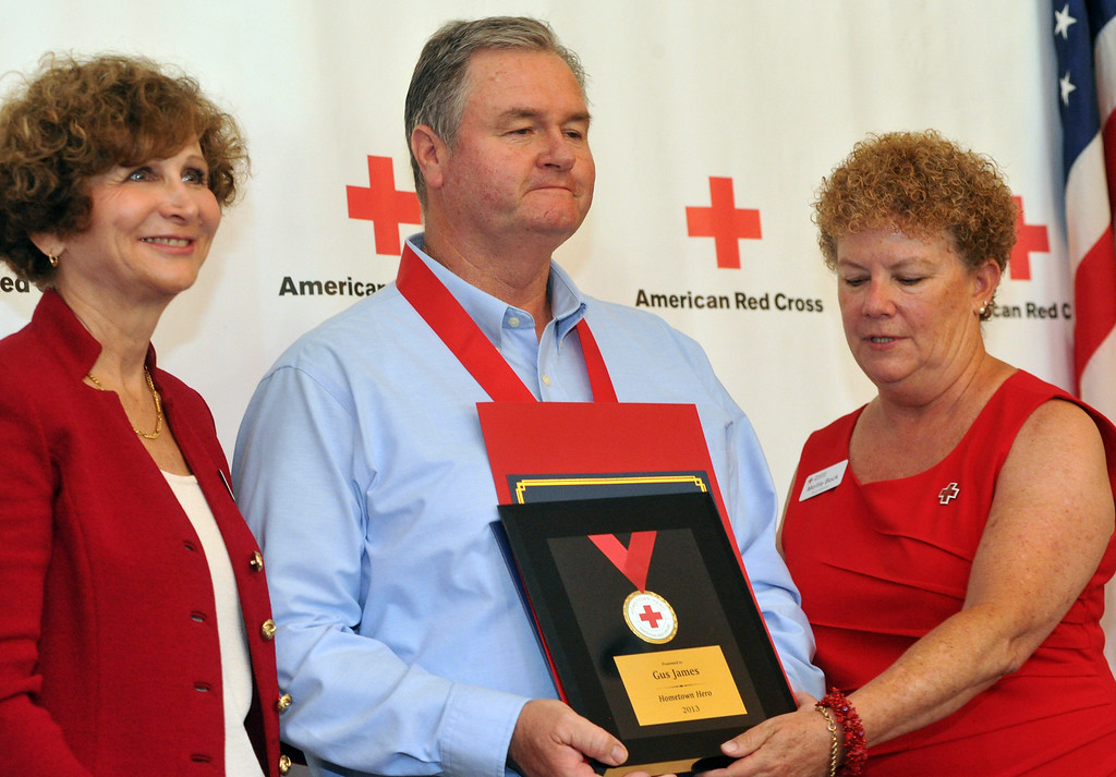 . Gus James, of La Mirada, shows plaque he received as the the Rio Hondo Chapter of the American Red Cross honors 14 people for their part in performing extraordinary acts during their Hometown Heroes luncheon at the Quiet Cannon in Montebello on Thursday June 27, 2013. (SGVN/Staff Photo by Keith Durflinger)