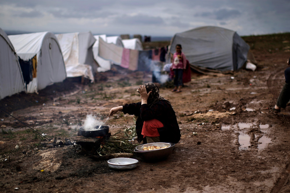 . A Syrian woman who fled her home cooks for her family outside her tent at a camp for displaced Syrians in the village of Atmeh, Syria, Tuesday, Dec. 11, 2012. This tent camp sheltering some of the hundreds of thousands of Syrians uprooted by the country\'s brutal civil war has lost the race against winter: the ground under white tents is soaked in mud, rain water seeps into thin mattresses and volunteer doctors routinely run out of medicine for coughing, runny-nosed children. (AP Photo/Muhammed Muheisen)