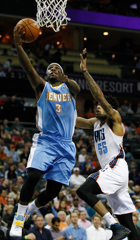 . Denver Nuggets guard Ty Lawson, left, drives for a lay up past Charlotte Bobcats guard Chris Douglas-Roberts during the second half of an NBA basketball game in Charlotte, N.C., Monday, March 10, 2014. Charlotte won 105-98. (AP Photo/Nell Redmond)