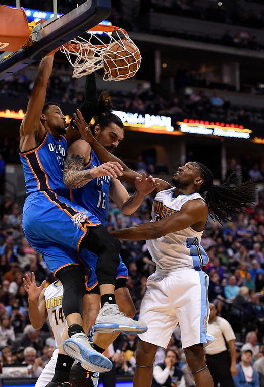 . Oklahoma City Thunder guard Andre Roberson (21) goes up for a big dunk over his teammate Oklahoma City Thunder center Steven Adams (12) as Denver Nuggets forward Kenneth Faried (35) looks on April 5, 2016 at Pepsi Center. (Photo By John Leyba/The Denver Post)
