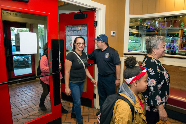 09/25/19 Wesley Bunnell | StaffrrTip a Firefighter took pace at Chili's in New Britain on Wednesday night. The event raised money for the city 's partnership with the community foundation regarding the new disaster relief program. Firefighter Marco Costa opens the door for Kaylano Ocasio, L, mother Tamika Ocasio, daughter Kasiyah Ocasio and grandmother Rose Bracero.