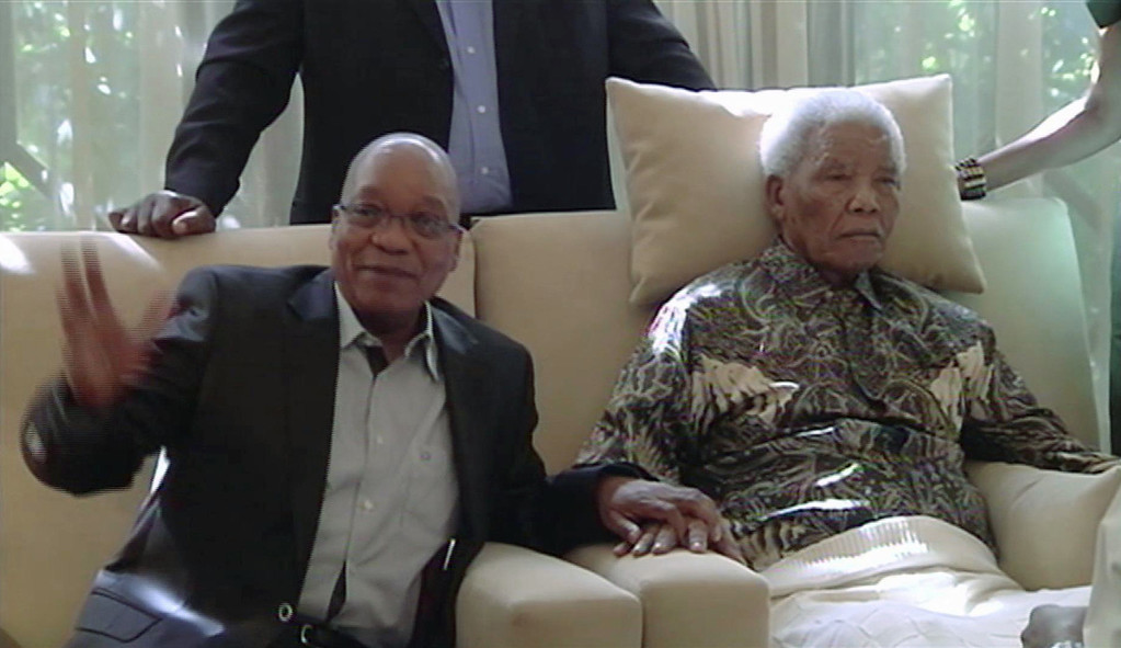 . In this image taken from video, South African President Jacob Zuma, left, sits with the ailing anti-apartheid icon Nelson Madela is filmed Monday April 29, 2013, more than three weeks after being released from hospital. Mandela was treated in hospital for a recurring lung infection.  South African President Jacob Zuma visited the former leader on April 29, but Mandela does not appear to speak during the televised portion of the visit, as he sits in an armchair, his head propped up by a pillow and with his cheeks showing what appear to be marks from a recently removed oxygen mask, although Zuma said he found Nelson Mandela �in good shape and in good spirits�.  After the encounter at Mandela�s home, Zuma cheerily said the 94-year-old was up and about, in good spirits and doing well.  (AP Photo/SABC TV)