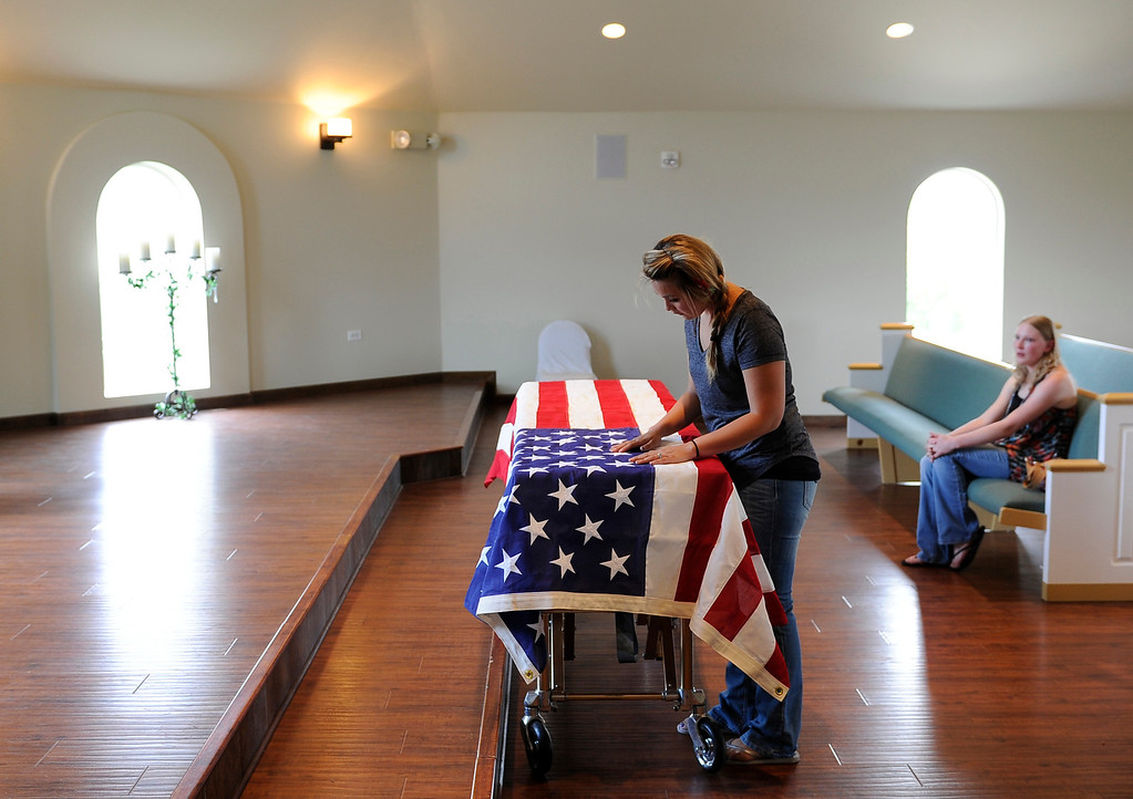. Chantel Blunk cleans lint off the flag draped over her husband Johnathan Blunk\'s casket at Apollo and Three Tree Chapel in Littleton on Friday, July 27, 2012. Blunk\'s casket was being prepared to be flown to Reno, Nevada for his full military funeral. Blunk, a five-year U.S. Navy veteran, was killed when James Holmes opened fire at a crowded movie theater. RJ Sangosti, The Denver Post