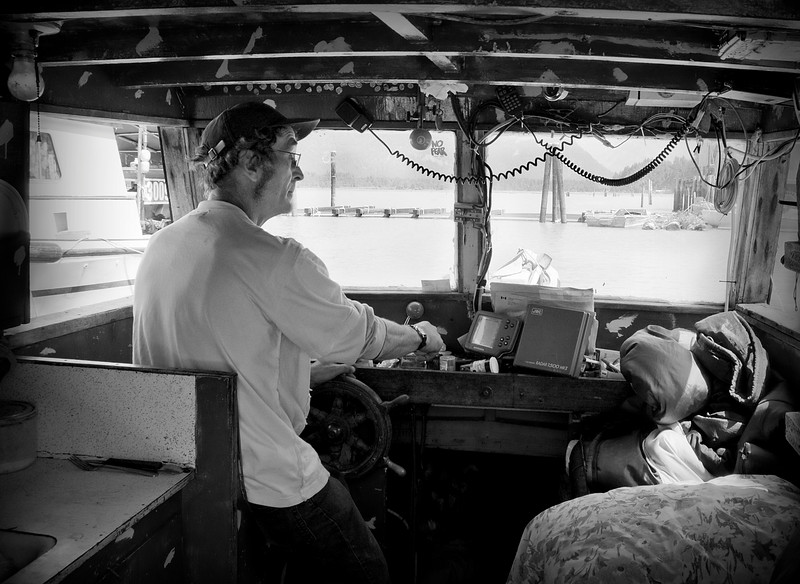 """Captain Fred Dorsey, a commercial fisherman at the helm of his vessel """"Marjorie"""", enroute to the Talheo Cannery."""