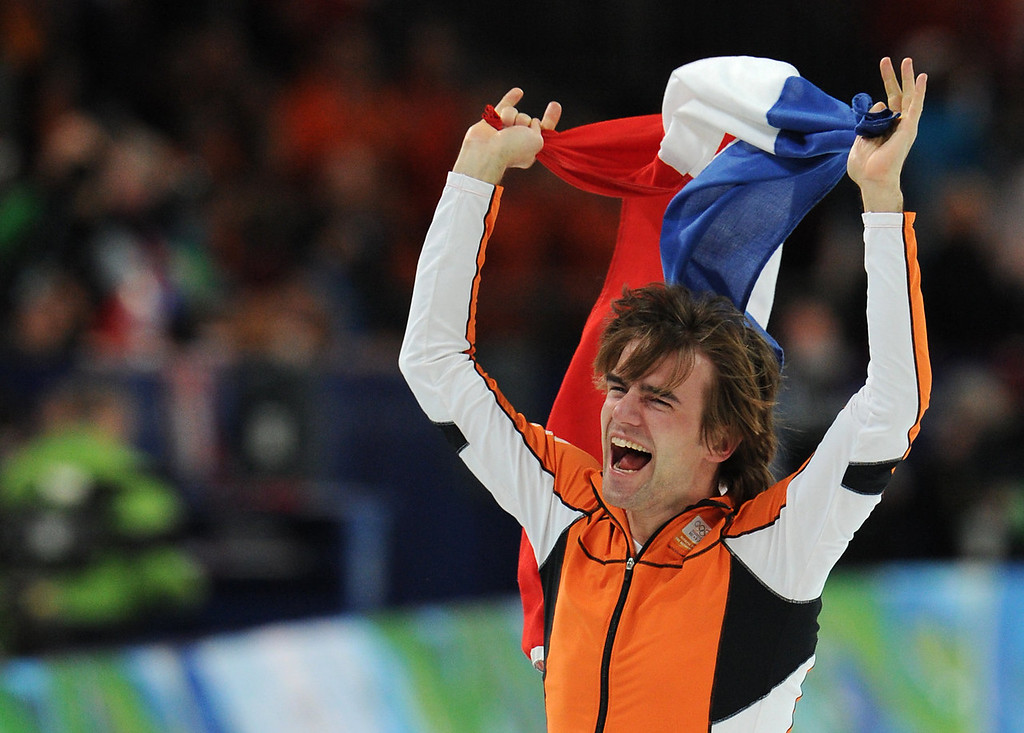 . Mark Tuitert (R) of the Netherlands celebrates with the Dutch flag after winning the 2010 Winter Olympics  men\'s 1,500m speedskating event at the Olympic Oval in Richmond, outside Vancouver on February 20, 2010.           AFP PHOTO/Saeed KHAN