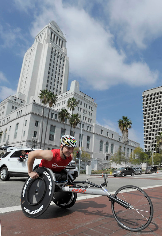 """. Ryan Chalmers wheels past Los Angeles City Hall. Chalmers is pushing himself in a wheel chair on a coast-to-coast trip that starts at the JW Marriott in Los Angeles, and will end in New York\'s Central Park. The 3000 mile odysey will raise funds for an organization called  \""""Stay Focused\"""" that allows teens and young adults with disabilities to participate in sports alongsid able-bodied people.  Los Angeles CA 4/6/2013(John McCoy/Staff Photographer"""