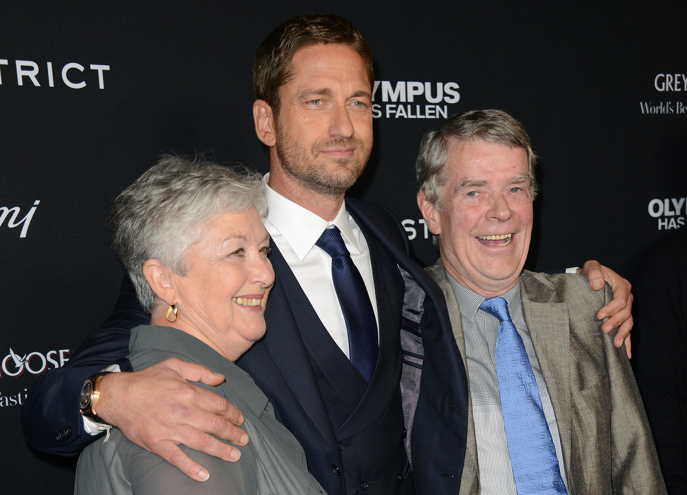 """. Gerard Butler, center, arrives with his parents at the LA premiere of \""""Olympus Has Fallen\"""" at the ArcLight Theatre on Monday, March 18, 2013 in Los Angeles. (Photo by Jordan Strauss/Invision/AP)"""