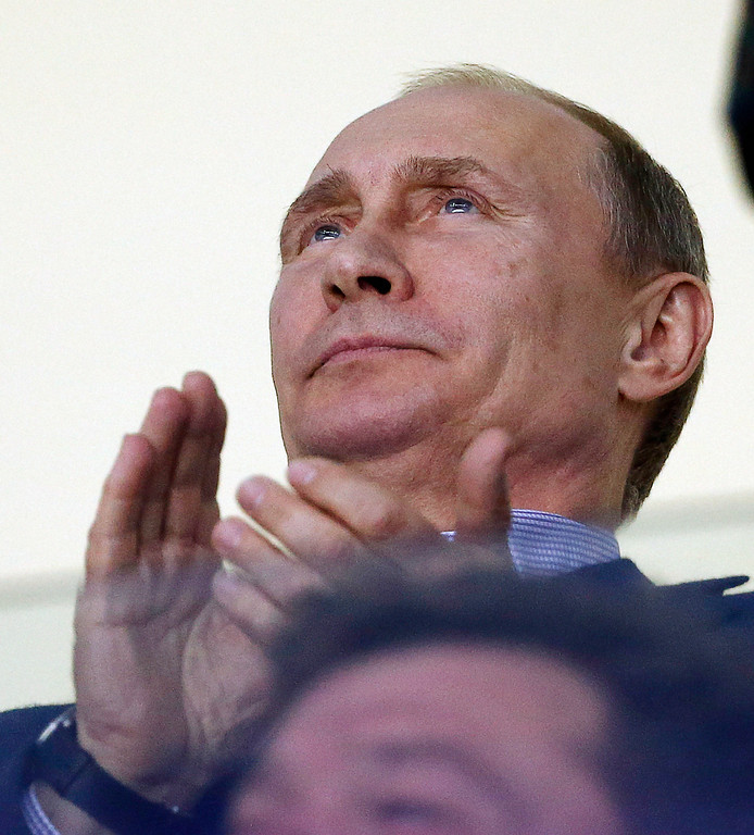 . Russian President Vladimir Putin claps during the third period of a men\'s ice hockey game between the USA and Russia at the 2014 Winter Olympics, Saturday, Feb. 15, 2014, in Sochi, Russia. (AP Photo/Petr David Josek)