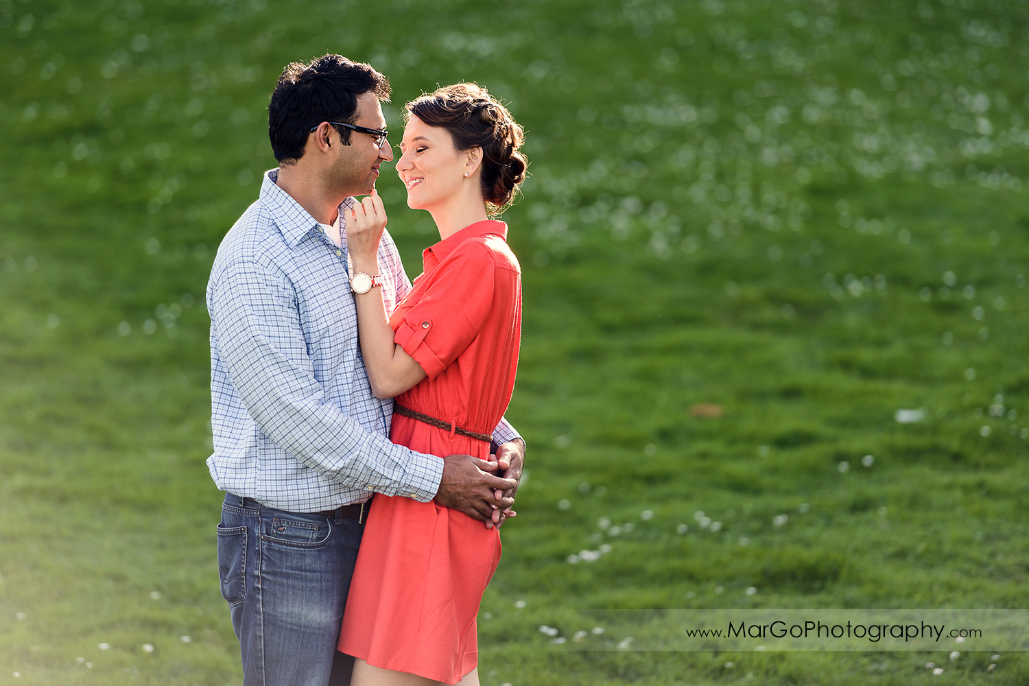 3/4 portarit of man in blue shirt and woman in red dress lokking at each other and standing on the grass during engagement session at San Francisco Legion of Honor