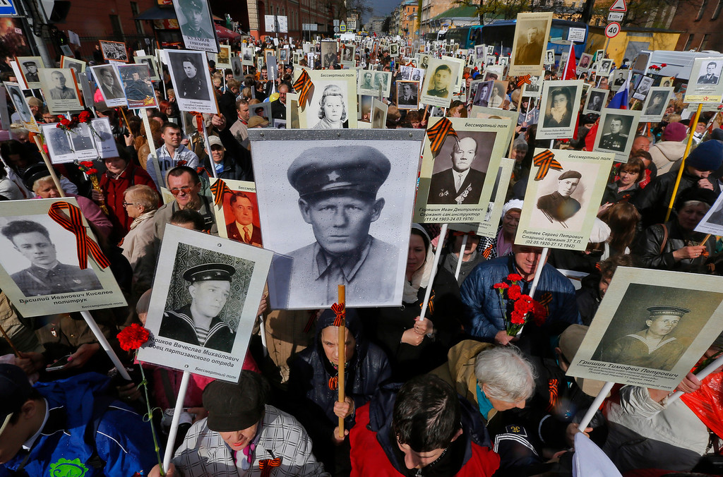 . Local residents carry portraits of their ancestors, participants of World War Two, as they celebrate Victory Day in St.Petersburg, Russia, Friday, May 9, 2014. About 30,000 people walked in central streets in march named \'Immortal regiment\' while carrying portraits of their relatives who fought in World War Two. Victory Day, marking the defeat of Nazi Germany, is Russia\'s most important secular holiday, celebrated on May 9. (AP Photo/Dmitry Lovetsky)