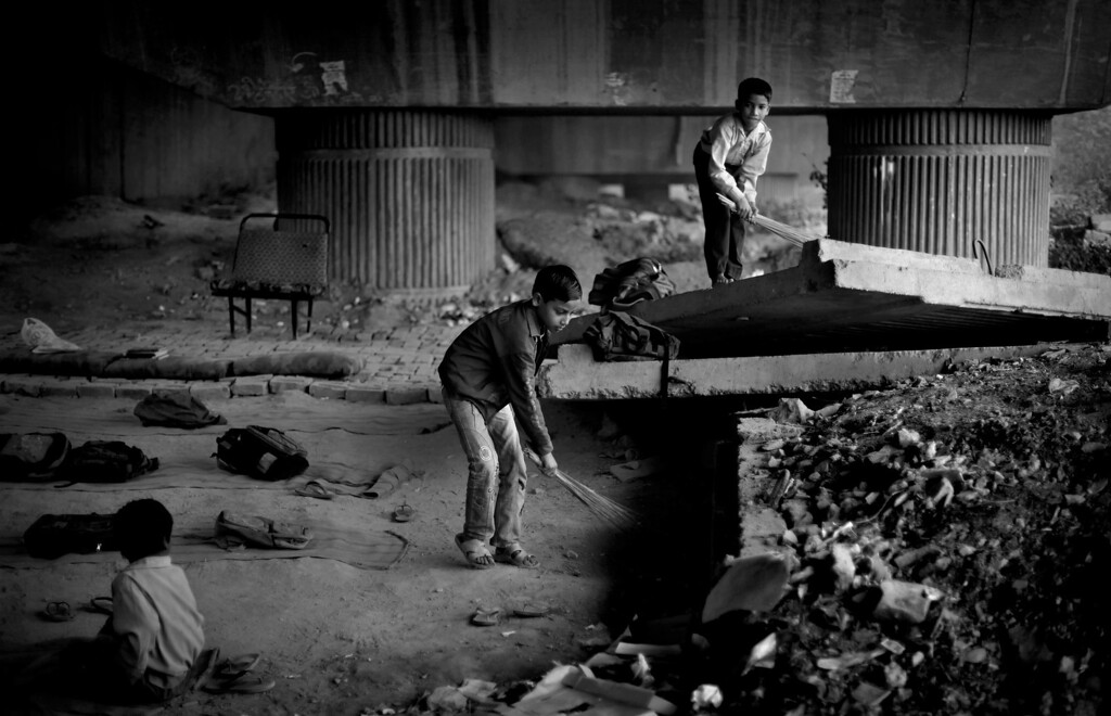 . In this Nov. 7, 2012 file photo, underprivileged Indian children clean a portion of a free school run under a metro bridge, which they attend, before the commencement of routine classes in New Delhi, India, Wednesday, Nov. 7, 2012.  This photo was one in a series of images by Associated Press photographer Altaf Qadri that received an honorable mention in the World Press Photo 2013 photo contest for the Contemporary Issues series category. (AP Photo/Altaf Qadri, File)